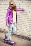 Adolescente rubio en un monopatín Fotografía de archivo libre de regalías