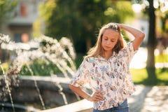 Adolescente rubio en una blusa rubia que juega con su pelo en el fondo de una fuente Imagen de archivo libre de regalías