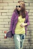 Adolescente rubio en vaqueros y gafas de sol con el monopatín Fotos de archivo