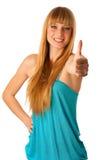 Adolescente rubio hermoso que muestra el pulgar para arriba como muestra del allr Fotografía de archivo