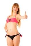 Adolescente rubio hermoso que muestra el pulgar para arriba como muestra del allr Imagen de archivo libre de regalías