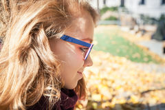 Adolescente rubio hermoso sonriente en vidrios Imagenes de archivo