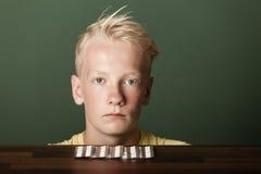 Adolescente rubio hosco con las tabletas en paquetes Imagen de archivo