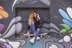 Adolescente rubio joven con un monopatín en una pared de la pintada Foto de archivo