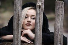Adolescente rubio lindo con las figuras agradables que se colocan detrás de la cerca de madera Fotografía de archivo libre de regalías