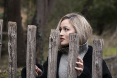Adolescente rubio lindo con las figuras agradables que se colocan detrás de la cerca de madera Imagen de archivo