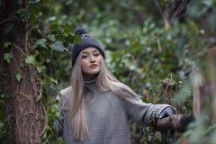 Adolescente rubio lindo con las figuras agradables que se inclinan en la cerca de madera Fotos de archivo