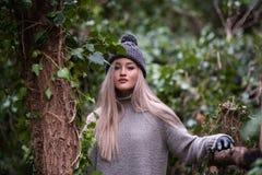 Adolescente rubio lindo con las figuras agradables que se inclinan en la cerca de madera Imagenes de archivo