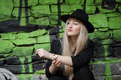 Adolescente rubio lindo contra la pared de piedra con la pintada verde Fotos de archivo libres de regalías