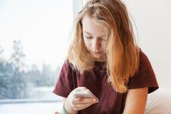 Adolescente rubio que se sienta con smartphone Fotos de archivo