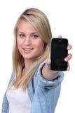 Adolescente rubio que sostiene el teléfono Imagen de archivo libre de regalías