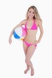 Adolescente rubio que sostiene una pelota de playa bajo su brazo Fotos de archivo