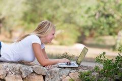 Adolescente rubio que usa el ordenador portátil al aire libre Imagenes de archivo