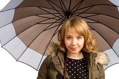 Adolescente rubio sonriente bajo un paraguas Fotografía de archivo libre de regalías