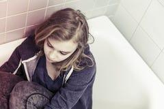 Adolescente rubio triste subrayado que se sienta en baño Foto de archivo libre de regalías