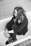 Adolescente rubio triste subrayado que se sienta en baño vacío Fotos de archivo libres de regalías