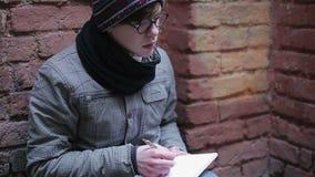 Adolescente só que escreve para baixo memórias, emoções e sentimentos tristes no diário video estoque