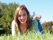 Adolescente s'étendant dans l'herbe photo stock