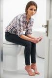 Adolescente s'asseyant dans la salle de bains avec l'essai de grossesse Photo stock