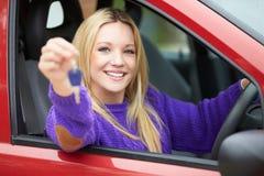 Adolescente s'asseyant dans la voiture tenant la clé Photos stock