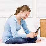 Adolescente s'asseyant sur la messagerie textuelle de bâti Photographie stock libre de droits