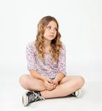Adolescente s'asseyant sur le plancher avec le visage triste Photo stock
