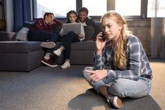 Adolescente s'asseyant sur le plancher et parlant sur le smartphone tandis qu'amis à l'aide de l'ordinateur portable derrière Photographie stock libre de droits