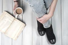 Adolescente s'asseyant sur le plancher tenant une tasse de café Photos stock