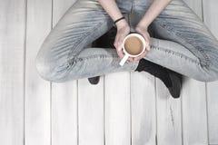 Adolescente s'asseyant sur le plancher tenant une tasse de café Photographie stock libre de droits