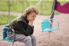 Adolescente s? triste exterior no campo de jogos as dificuldades da adolesc?ncia no conceito de uma comunica??o imagens de stock