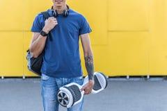 Adolescente saliente que sostiene hoverboard en brazo Fotos de archivo