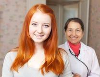 Adolescente sano feliz contra doctor Imagen de archivo libre de regalías