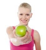 Adolescente sano que le ofrece la manzana verde Fotos de archivo