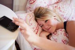 Adolescente se réveillant dans le lit et arrêtant l'alarme au téléphone Photographie stock libre de droits