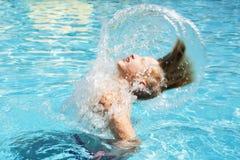 Adolescente se relaja en la piscina Foto de archivo libre de regalías
