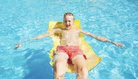 Adolescente se relaja en la piscina Fotografía de archivo libre de regalías
