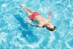 Adolescente se relaja en la piscina Imagenes de archivo