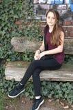 Adolescente se reposant dehors sur le vieux banc photos libres de droits