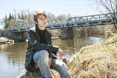 Adolescente se sienta afuera cerca de una chaqueta de cuero del puente Fotografía de archivo