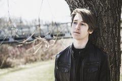 Adolescente se sienta afuera cerca de una chaqueta de cuero del puente Foto de archivo