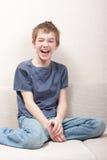 Adolescente se sienta en el sofá y ríe Fotografía de archivo libre de regalías
