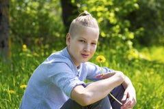 Adolescente se sienta en la hierba Fotos de archivo