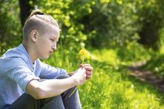 Adolescente se sienta en la hierba Imagen de archivo libre de regalías