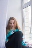 Adolescente se sienta en la ventana y la lectura de un libro en tableta Fotos de archivo