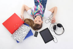 Adolescente se trouvant avec le PC, le téléphone et les écouteurs de tablette Photo stock