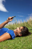 Adolescente se trouvant sur l'herbe avec le joueur mp3 Photographie stock