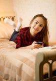 Adolescente se trouvant sur le lit et le message de dactylographie Photographie stock