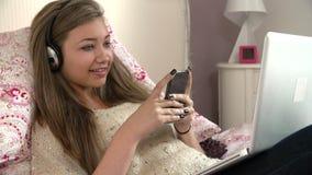 Adolescente se trouvant sur le lit utilisant l'ordinateur portable tout en textotant banque de vidéos