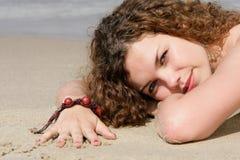Adolescente se trouvant sur le sable Photographie stock libre de droits