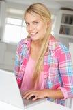 Adolescente sentado usando la computadora portátil Fotografía de archivo libre de regalías